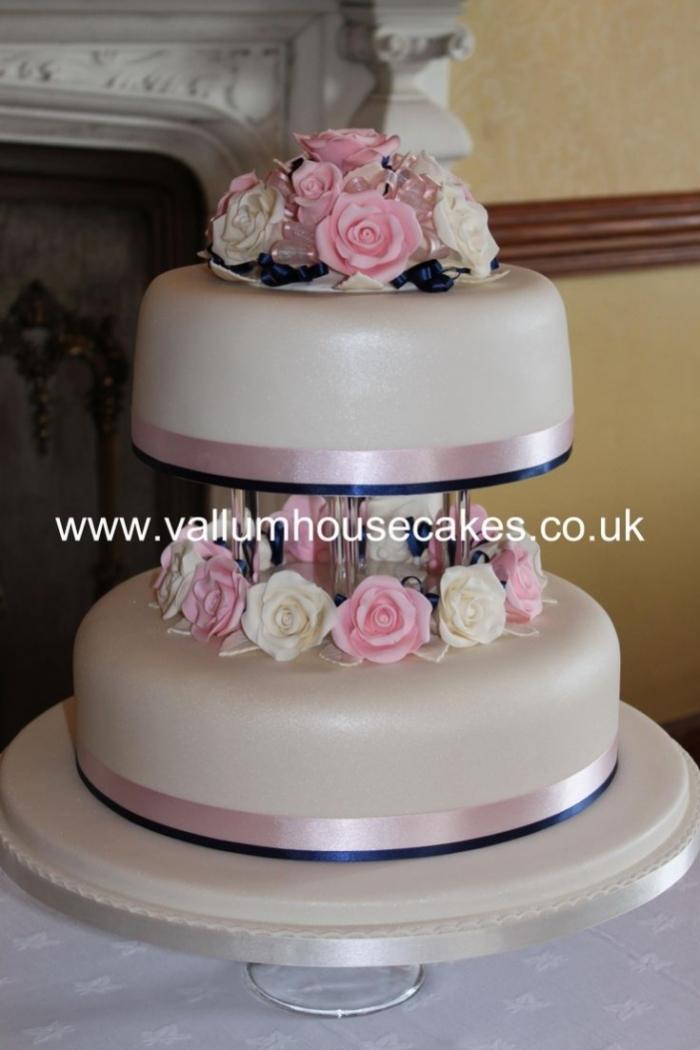 gâteau simple à 2 étages avec différentes fleurs avec rubans rose